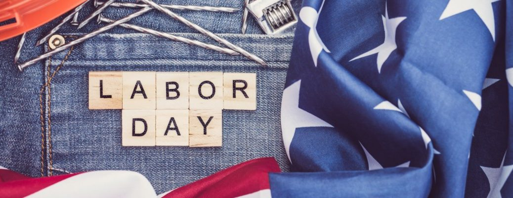 labor day written in wooden tiles upon a pair of jeans near an american flag, a wrench, nails, and an orange hard hat