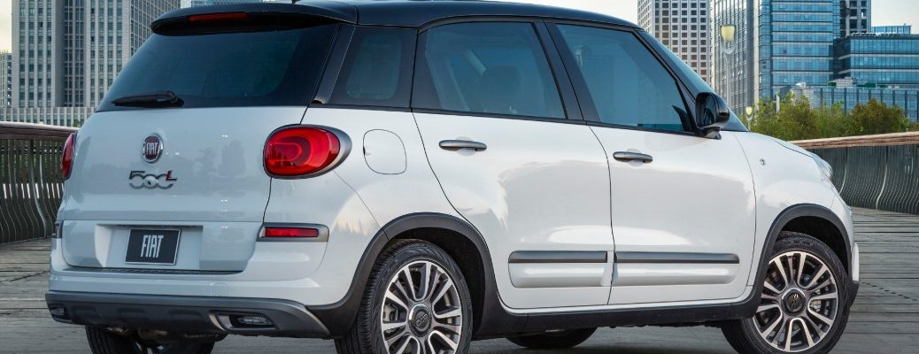 2020 Fiat 500L wagon with bianco white paint color exterior rear side shot parked on a bridge with a background of skyscrapers