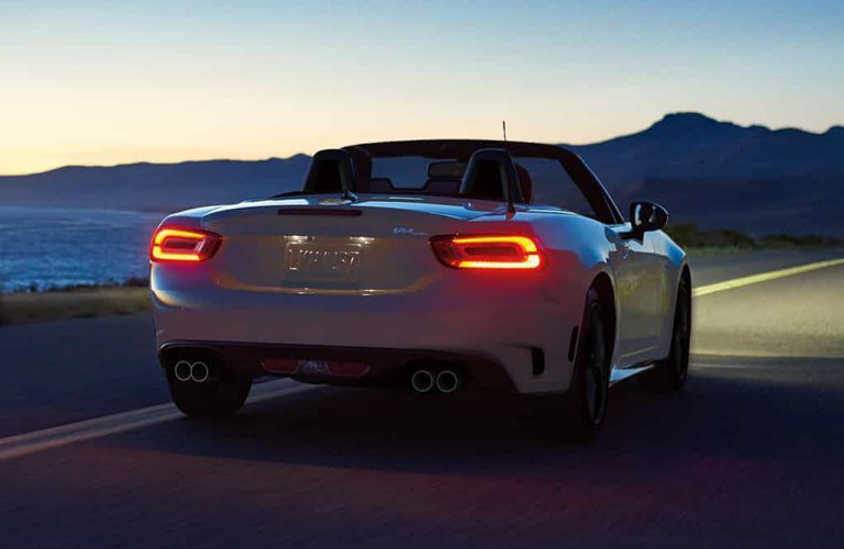Rear view of Fiat 124 Spider driving on open highway