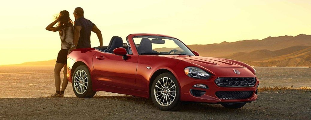 2020 Fiat 124 Spider roadster convertible exterior shot with hypnotique red paint color parked on a beach near the water as a couple watches the sunset