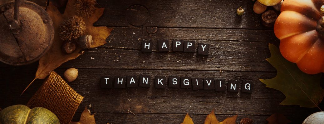 Happy Thanksgiving written out on small tiles on a wooden plank picnic table surrounded by leaves, nuts, and a pumpkin gourd