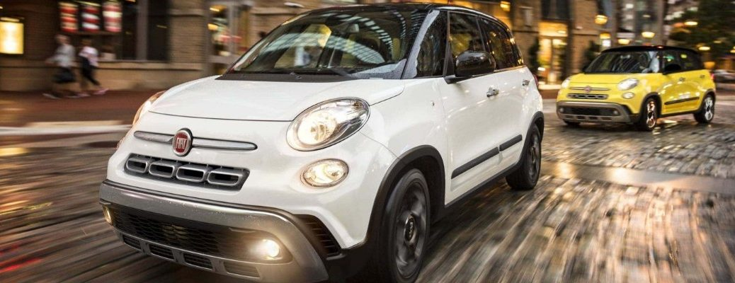 2020 Fiat 500L models in white and yellow driving through a city on a stone rock tile street as the lights blur in the background