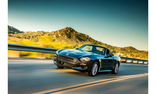 2020 Fiat 124 Spider Classica exterior shot with black paint color driving on a country highway past grassy hills