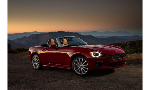 2020 Fiat 124 Spider Lusso exterior side shot with red paint color parked on a dirt road as the sun sets over hills