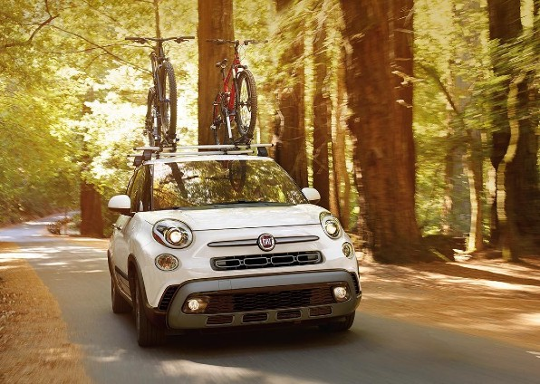 2019 Fiat 500L driving through the woods with bikes on the roof