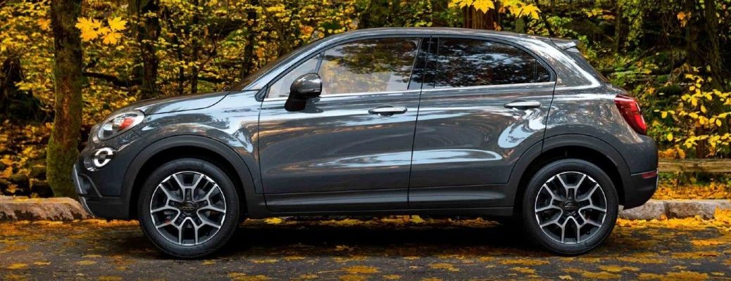 2020 Fiat 500X exterior side shot with grey metallic paint color parked on a road near forest trees with fall leaves on the ground
