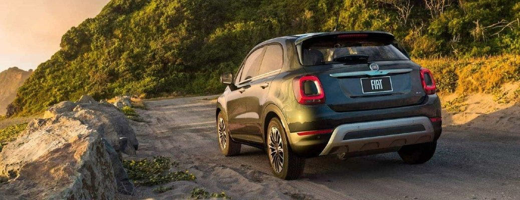 2020 Fiat 500X exterior rear shot with gray metallic paint color driving on a dirt road near rocks and grassy hills