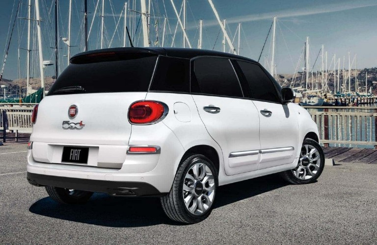 The rear and side view of a white 2020 Fiat 500L Lounge parked near a harbor.