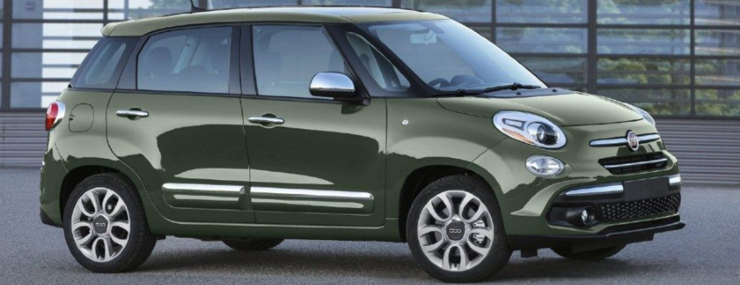 The side view of a dark green 2020 Fiat parked along a paved road.
