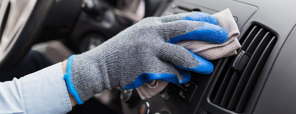 A gloved auto service staff hand cleaning a vehicle by wiping down the dashboard with a cleaning solution