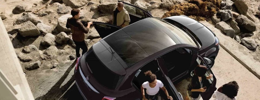 2020 Fiat 500X exterior overhead shot of dual-pane panoramic sunroof as a group of friends exit the vehicle onto a beach