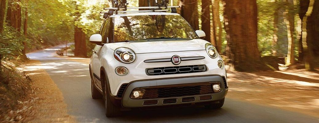 White 2020 Fiat 500L drives down a street in the woods