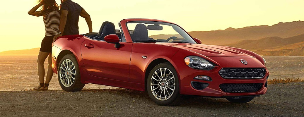 2020 Fiat 124 Spider red exterior front passenger side parked in desert couple leaning on trunk