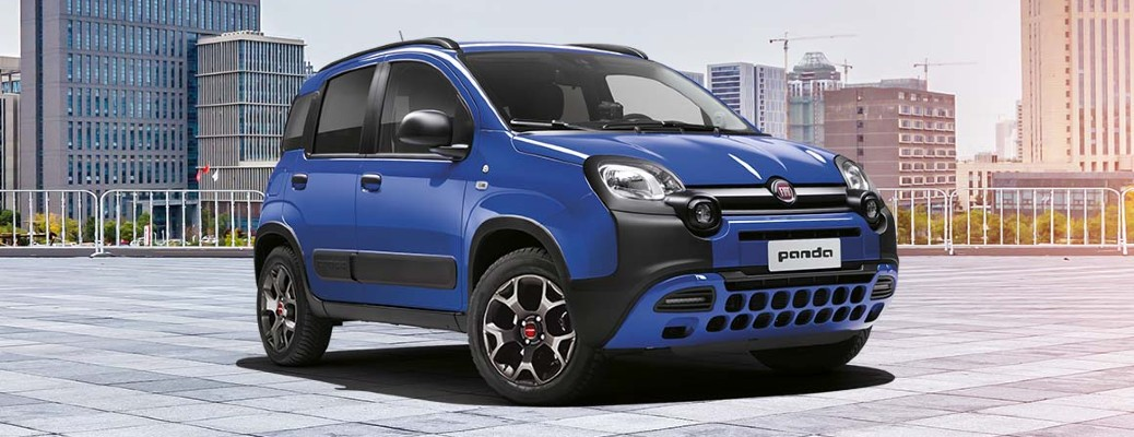 Fiat Panda exterior shot with blue paint color parked on a roof with a city skyline background