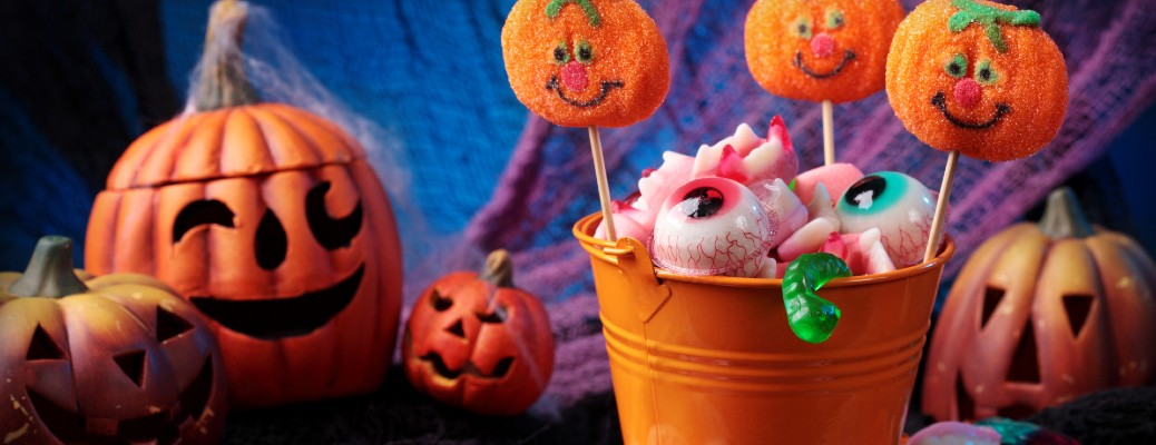 a bucket full of Halloween decorations, treats and candy with a winking plastic pumpkin in the background
