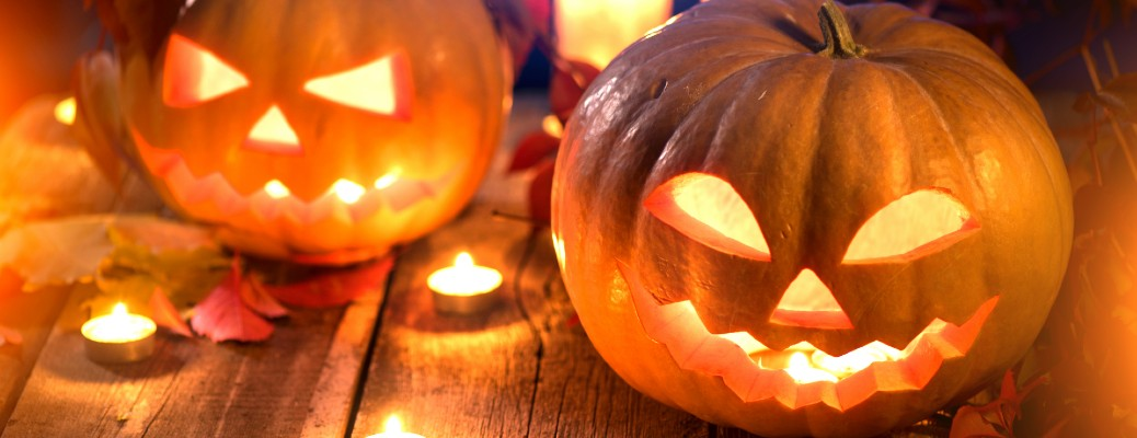 carved and lit jack o' lantern pumpkins on a wooden table surrounded by leaves and candles