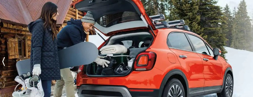 2020 Fiat 500X exterior rear shot of open trunk as a couple unloads winter gear outside of a forest cabin