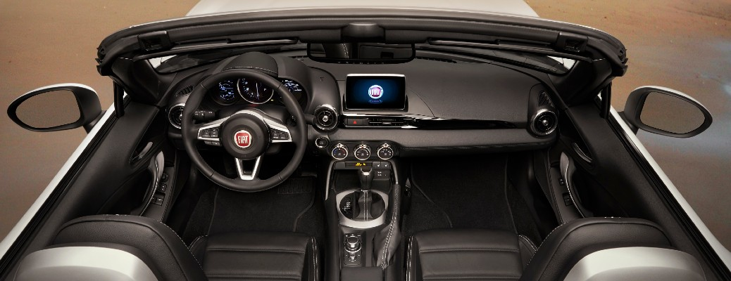 2020 Fiat 124 Spider exterior overhead shot with roof down showing front seating, steering wheel, and dashboard layout