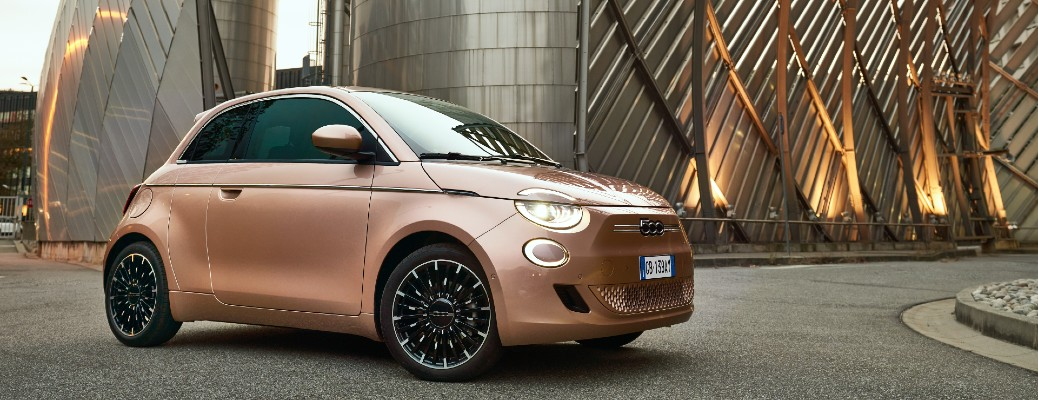 New Fiat 500 exterior shot with bronze paint color parked in front of a metal art sculpture