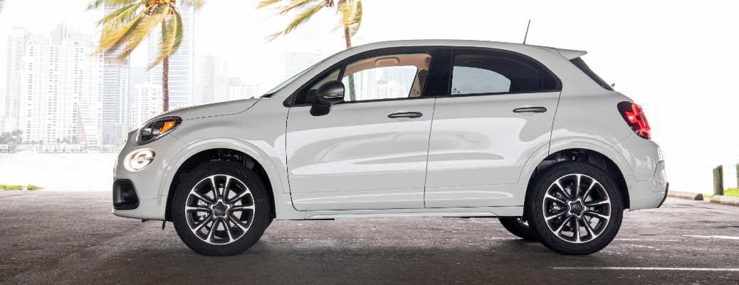 2021 Fiat 500X exterior side shot with white paint color and Sport Appearance Package parked under a bridge near palm trees and water