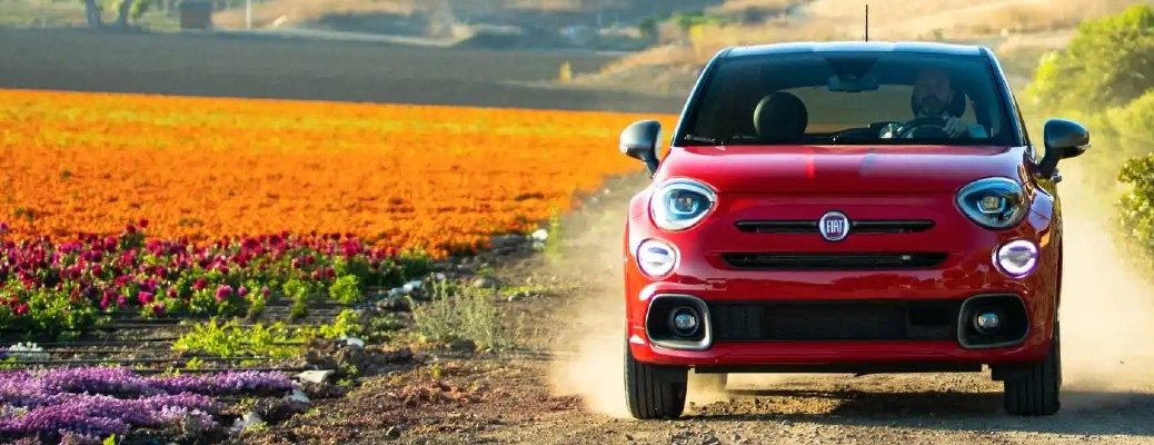 2021 Fiat 500X exterior front shot with red paint color driving on a gravel dirt road near colorful fields of flowers