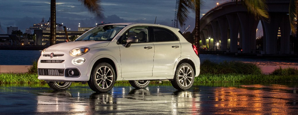 2021 Fiat 500X exterior shot in white paint color parked on a wet street near palm trees at night