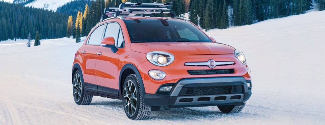 The front and side view of an orange 2017 Fiat 500X in the snow.
