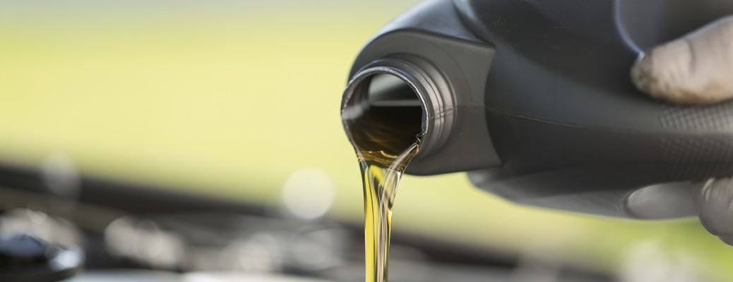 A mechanic pouring fresh oil into a vehicle.