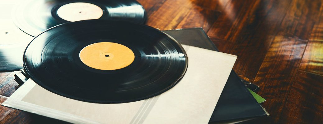 Two vinyl records positioned by their cases on wood table