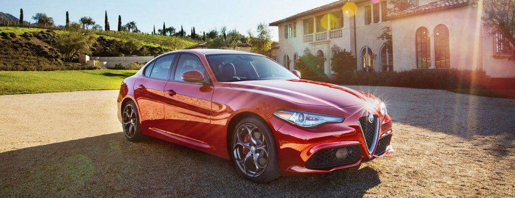 Profile view of red Alfa Romeo Giulia in front of Italian styled building