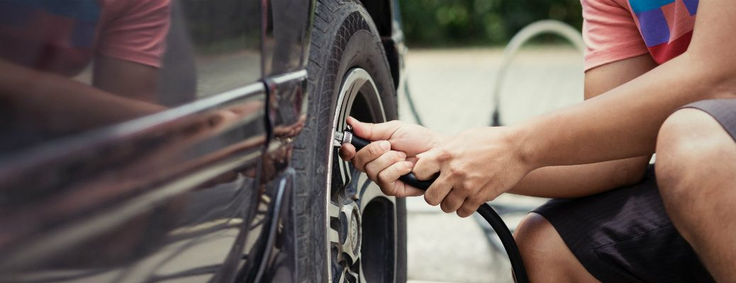 Checking the tire pressure on vehicle in daytime