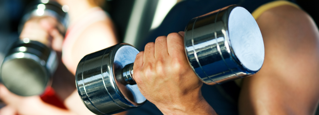 close up of man's arm curling dumbbell in gym