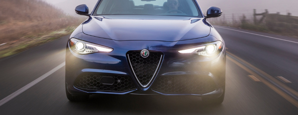 front view of 2019 alfa romeo giulia with headlights on driving in dark