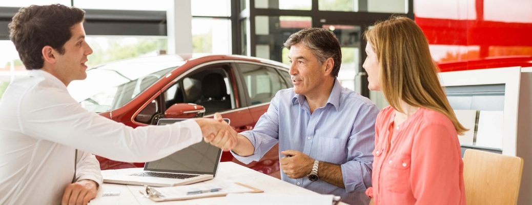 Male and female talking to car salesman in front of vehicle