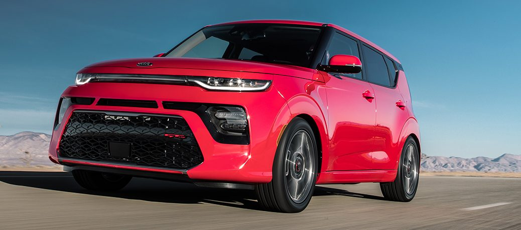 Exterior view of a red 2020 Kia Soul driving down a desert highway