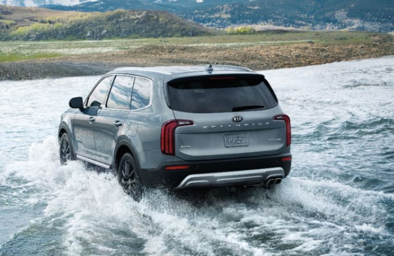Exterior view of the rear of silver 2020 Kia Telluride driving across a shallow river