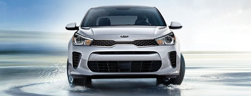 Exterior view of a 2019 Kia Rio driving on wet pavement