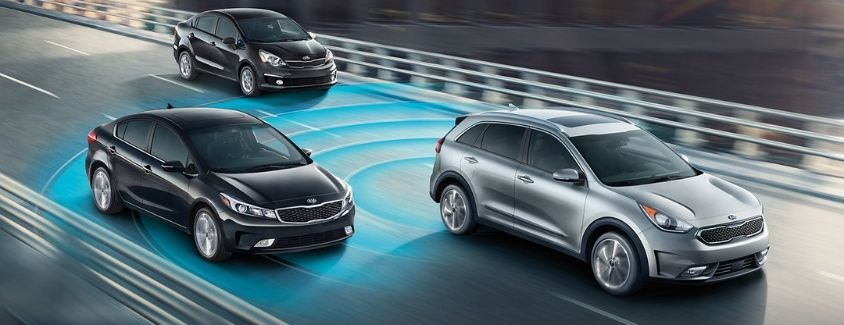 Exterior view of a silver 2019 Kia Niro driving on a bridge with a visual representation of blue radar lines showing the Blind Spot Detection Kia Drive Wise feature