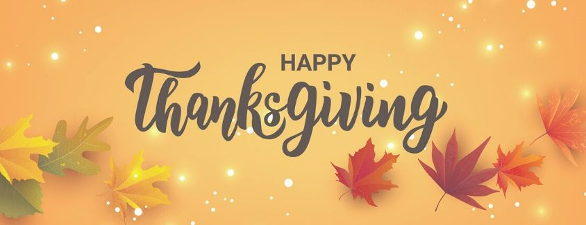 Happy Thanksgiving banner with a gold background and falling leaves