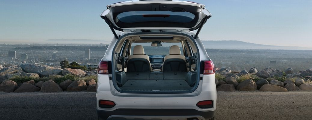 Exterior view of the rear of a white 2020 Kia Sorento with the rear hatch open highlighting the interior cargo area