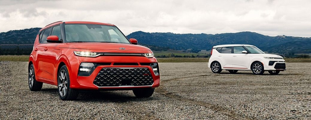 Exterior view of a red and a white 2020 Kia Soul parked near one another