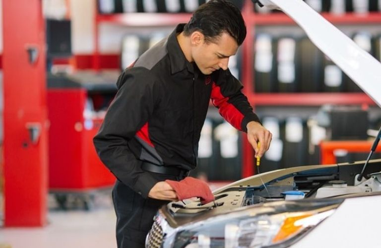 Image of a Toyota service technician changing a vehicle's oil