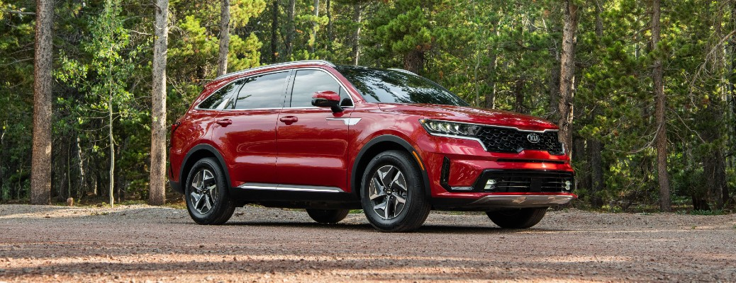 2021 Kia Sorento Hybrid exterior shot with Runway Red paint color parked in a forest clearing