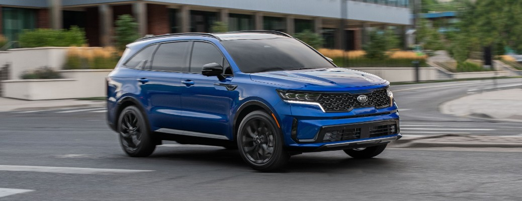 2021 Kia Sorento exterior shot with blue paint color driving past a building near a grass field