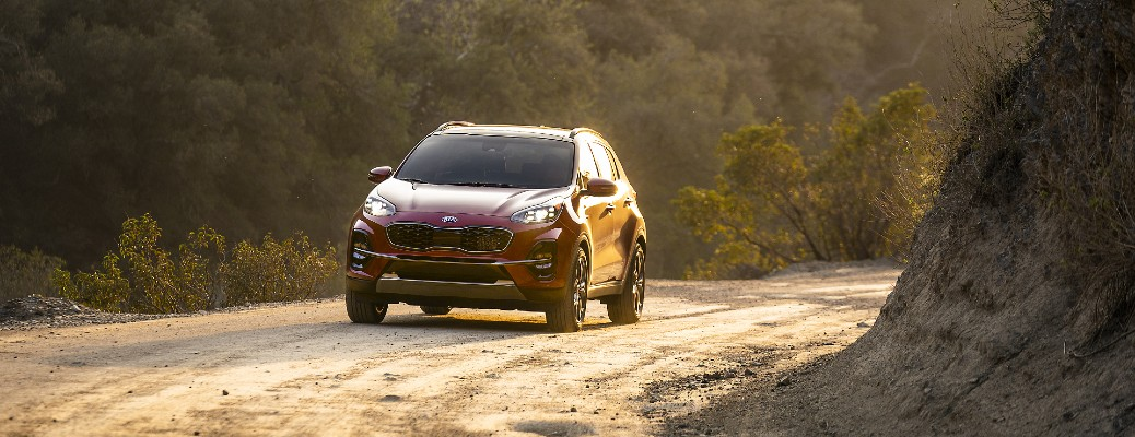2021 Kia Sportage SUV exterior far away shot with red paint color as it drives through a dirt gravel road in the wilderness under a setting sun