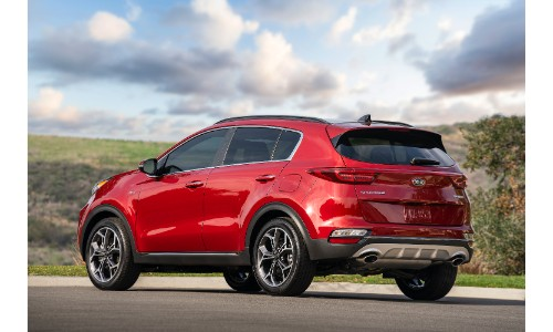 2021 Kia Sportage SUV exterior rear shot showing back bumper and taillight design while parked under a cloudy blue sky