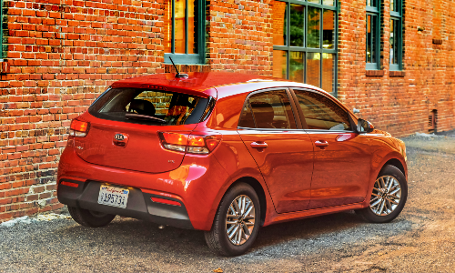 2020 Kia Rio 5-Door exterior rear shot with red paint color parked by a brick wall