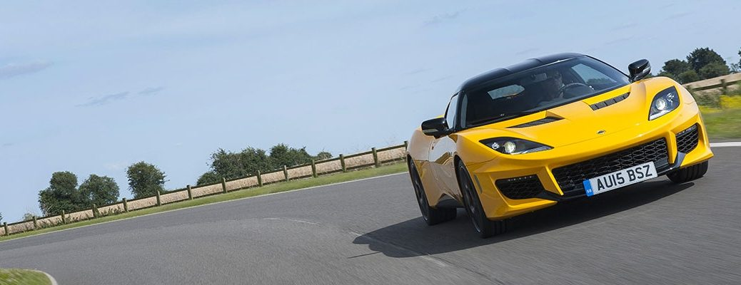 Exterior view of a yellow Lotus Evora 400 driving around an empty racetrack