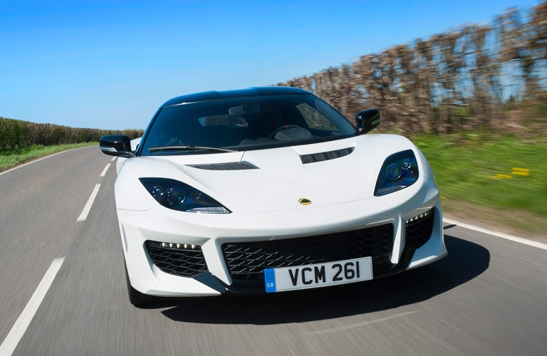 Exterior view of a white Lotus Evora 400 driving down the open road