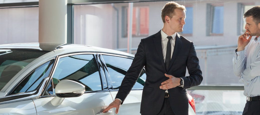 Two people discussing and looking at a car